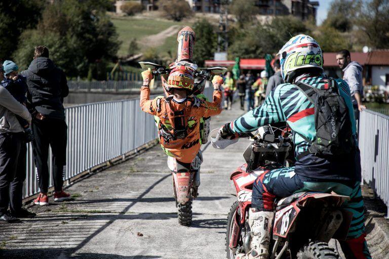Enduro rider doing a wheelie on a bridge