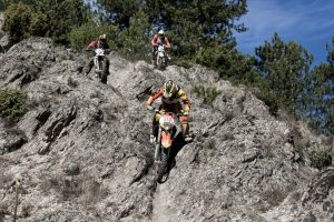 group of enduro riders going down a rocky section
