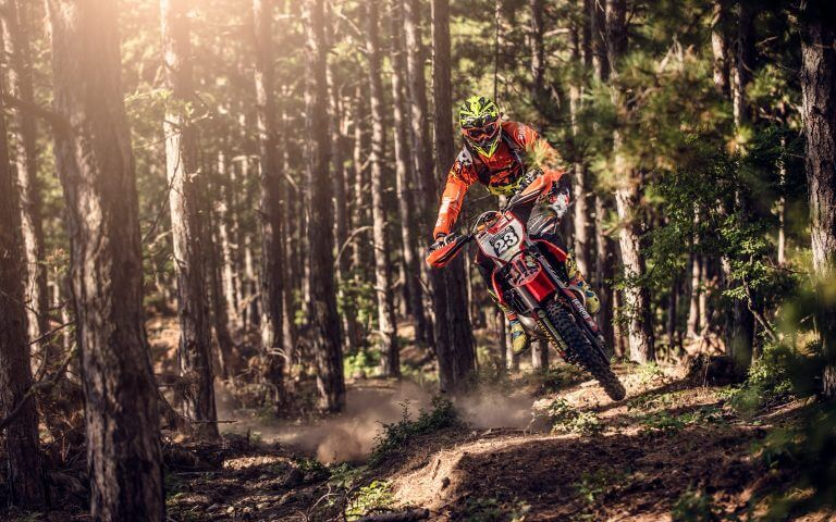 man jumping with a motorbike in the forest